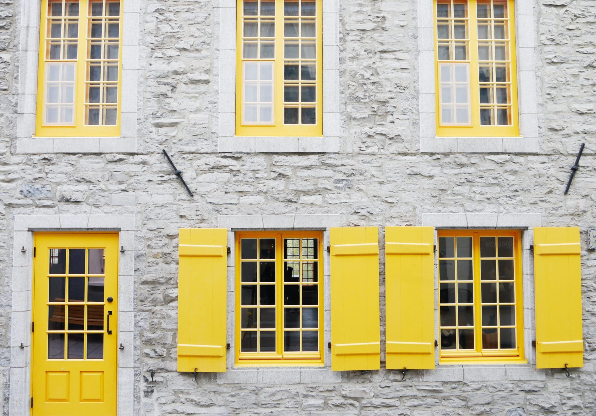 White, multi-story building with yellow windows and yellow door, signifying options for home inspection clients