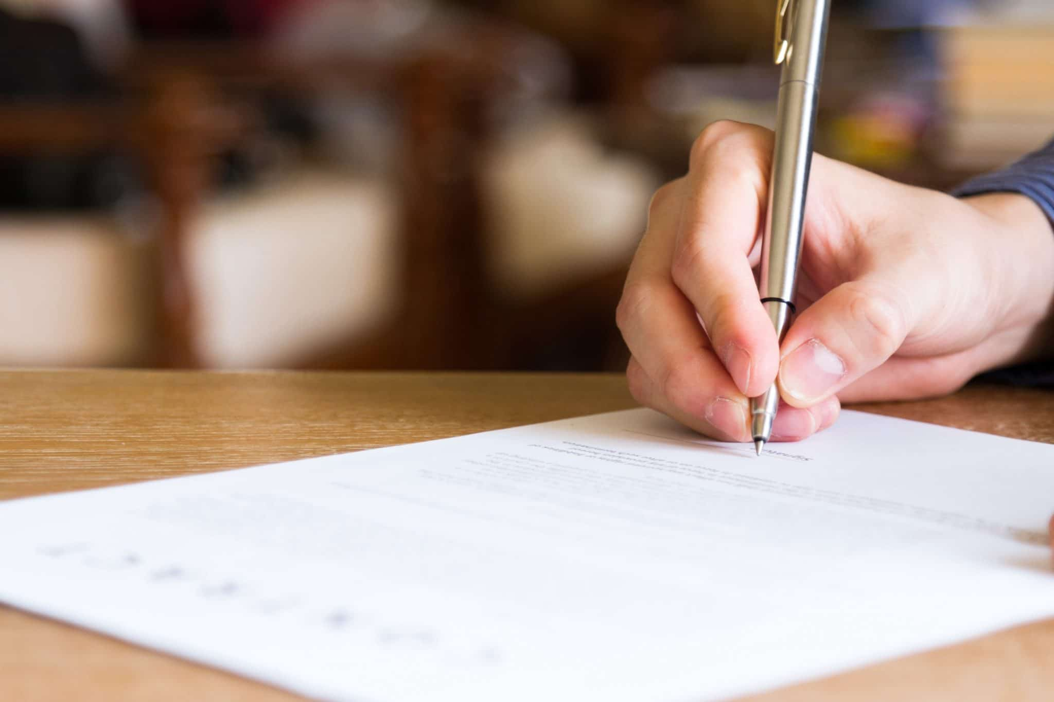 Hand holding pen to sign a printed document, just as a home inspection client must sign an agreement before their inspection