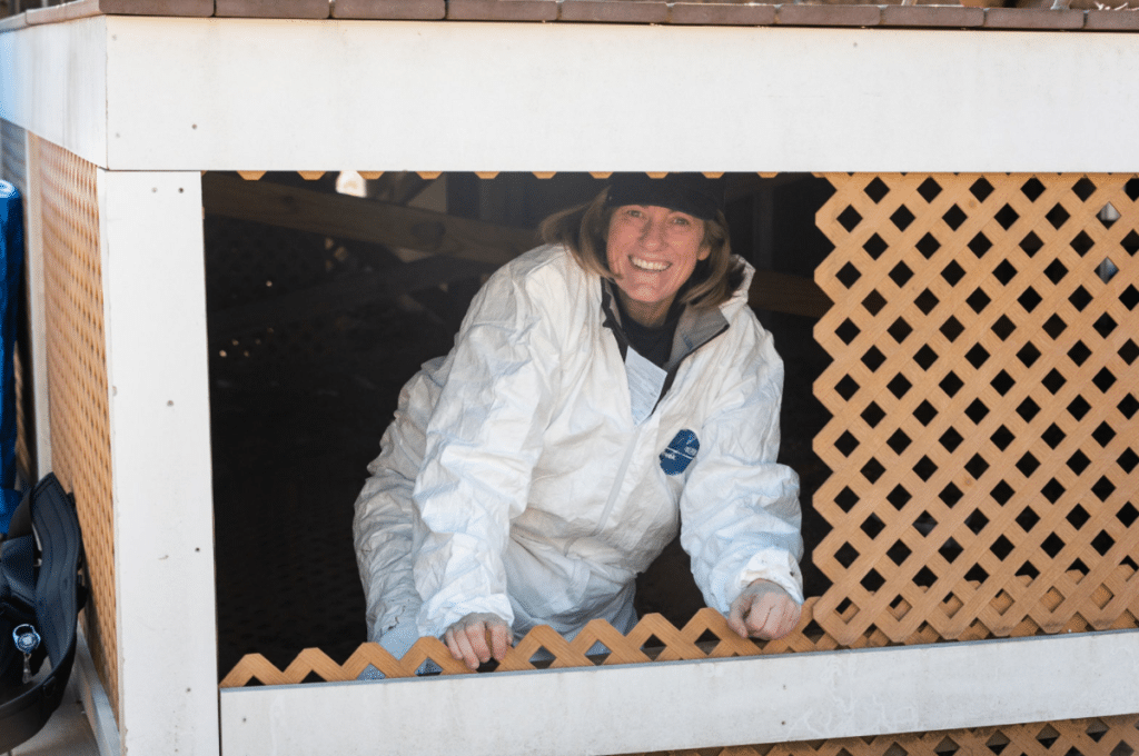 Alajajian Giroux smiling from a crawlspace during an inspection