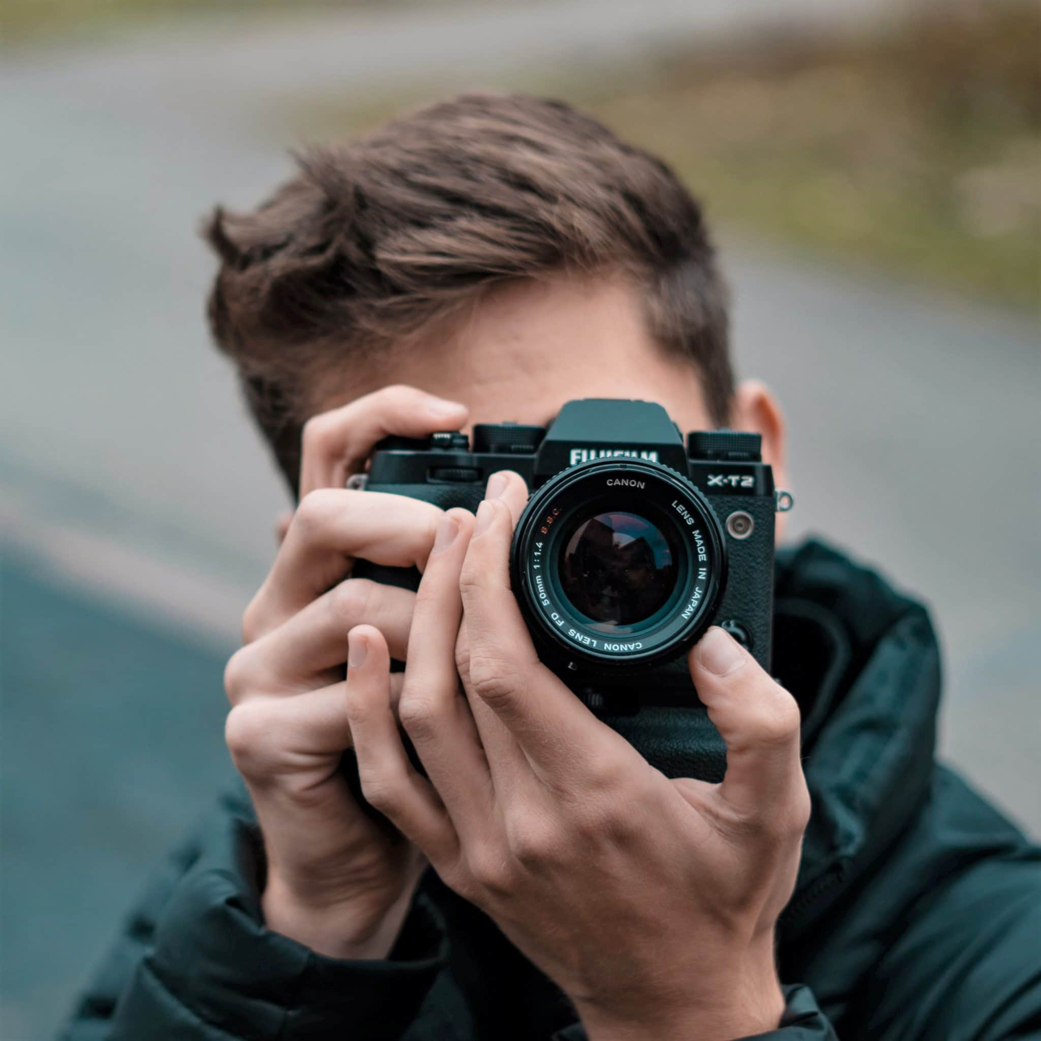 Man holding up DSLR camera in front of his face to take a photo