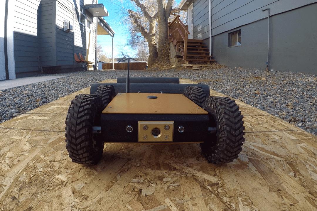 Close up of crawl bot moving toward camera, driving across plank of wood